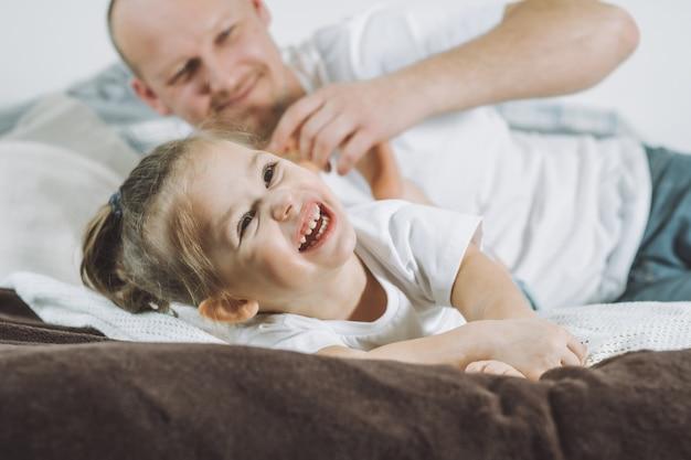 Pai brinca com a filha 2-4 na cama. papai faz cócegas nos pés das crianças. família se divertindo
