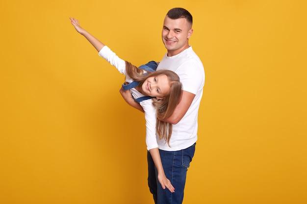 Pai brinca com menina bonitinha, criança vestida com roupas casuais, homem bonito, segurando sua filha como avião, isolado no amarelo. relações familiares