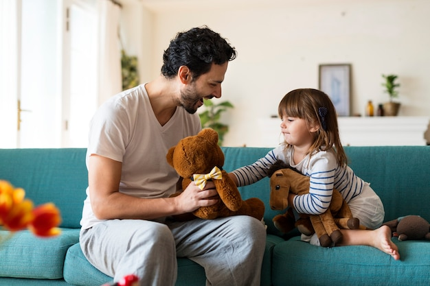 Pai brincando com a filha em uma sala de estar