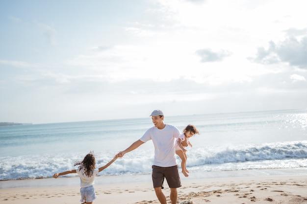Pai brincando com a filha na praia se divertindo juntos