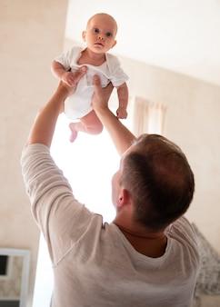 Pai brincando com bebê dentro de casa