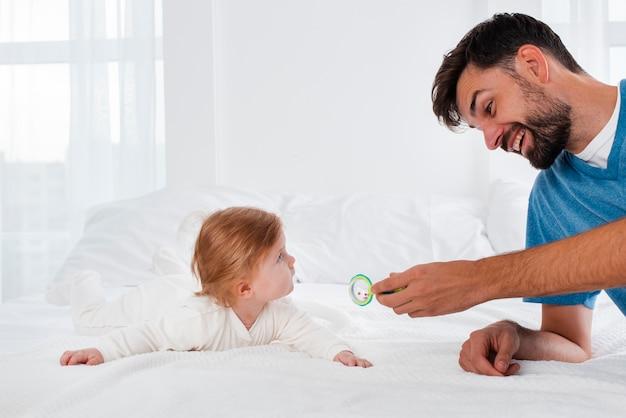Pai brincando com bebê sorridente