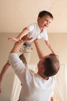 Pai brincando com criança dentro de casa
