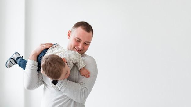 Pai brincando com criança e copie o espaço