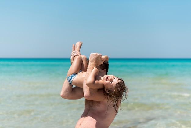 Pai brincando com filho à beira-mar