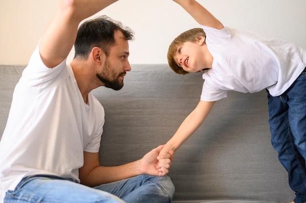 Pai brincando com filho no sofá