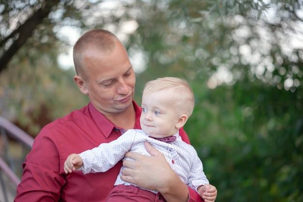 Pai brincando com filho pequeno na natureza. conceito de família feliz