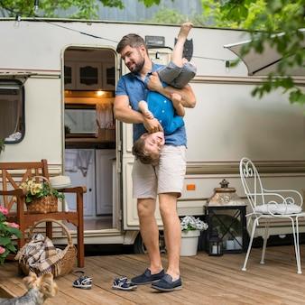Pai brincando com seu filho ao lado de uma caravana