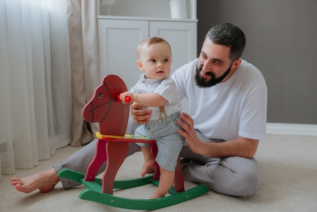 Pai brincando com seu filho bebê no quarto.