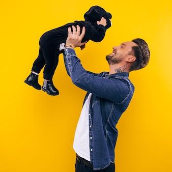 Pai brincando com seu filho, segurando-o nos braços.