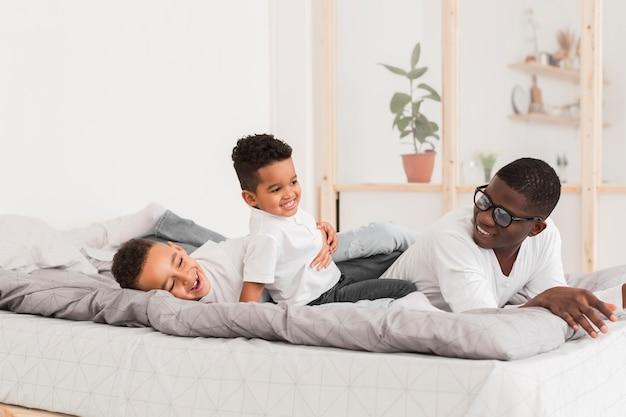 Pai brincando com seus filhos na cama
