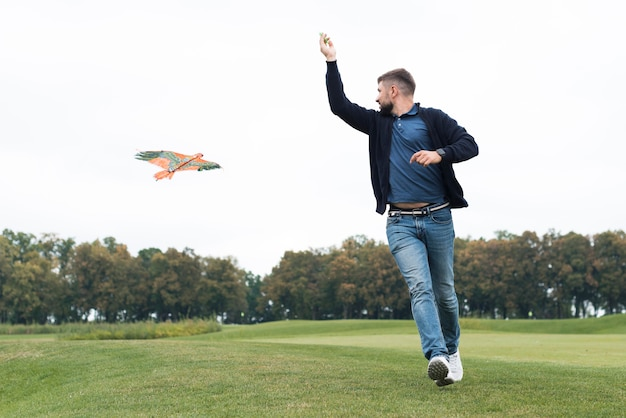 Pai brincando com uma pipa no parque