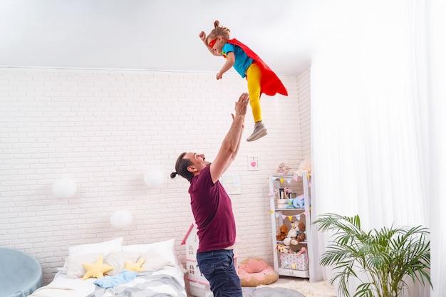 Pai brincando de super-heróis com seu filho