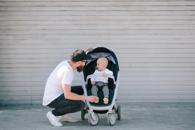Pai caminhando com um carrinho e um bebê nas ruas da cidade