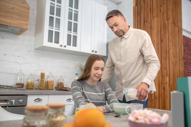 Pai carinhoso derramando leite em um prato com mingau para sua filha feliz no café da manhã.