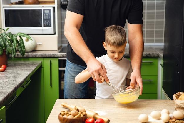 Pai carinhoso ensina o filho a cozinhar. atividade interna. ótimo tempo com a família