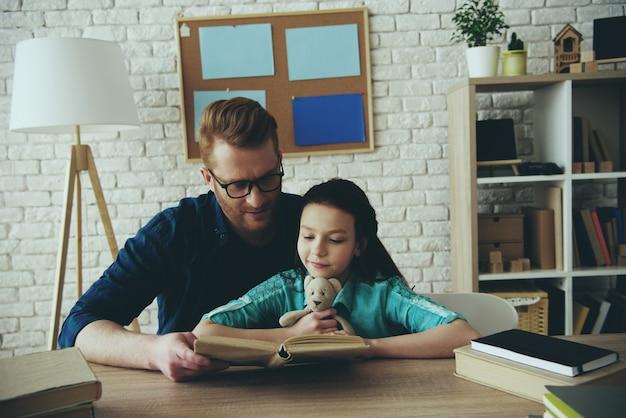 Pai carinhoso lê livro para filha.