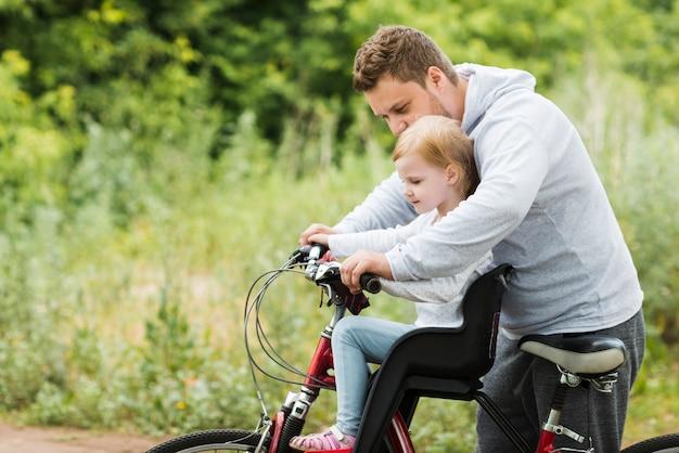 Pai carinhoso segurando a filha na bicicleta