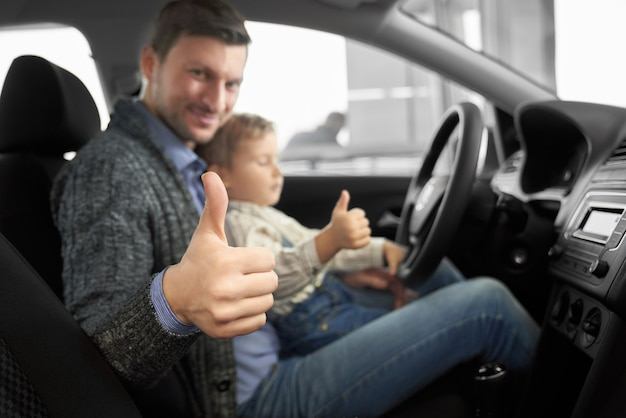 Pai carinhoso, sentado com o filho no novo automóvel confortável