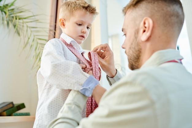Pai carinhoso vestir seu filho
