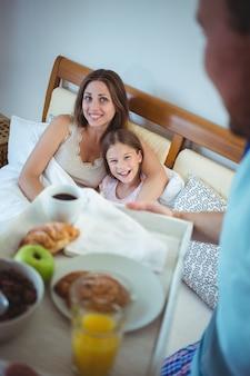 Pai carregando bandeja com café da manhã para mãe e filha