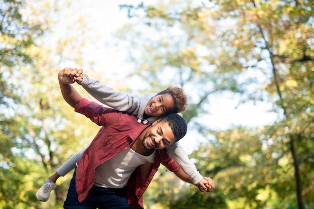 Pai carregando filha nas costas com os braços abertos