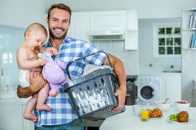 Pai carregando filho brincalhão, segurando o cesto por mesa