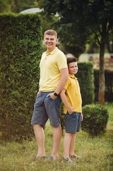 Pai caucasiano bonito posando para a câmera com seu filho pequeno no parque no verão