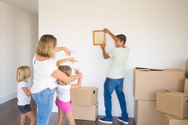 Pai caucasiano com roupas casuais pendurando moldura vazia na parede da nova casa e sorrindo