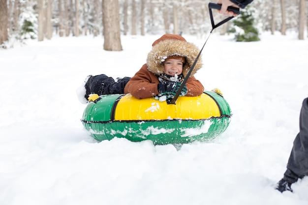 Pai cavalga filho em tubo de neve no inverno