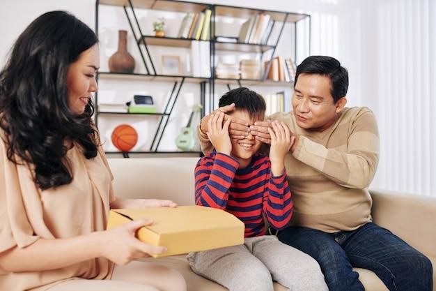 Pai cobrindo os olhos do filho pré-adolescente quando a mãe lhe dá um presente de aniversário