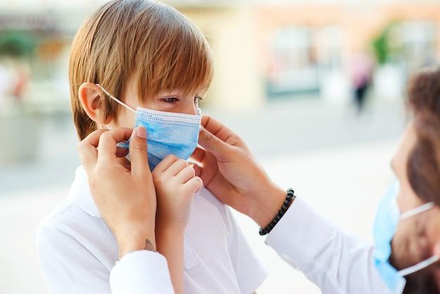 Pai colocando no filho uma máscara para proteger e prevenir o coronavírus.