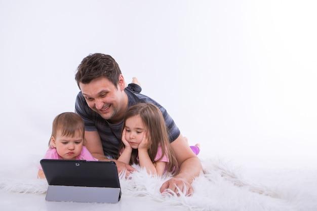 Pai com as crianças estão assistindo desenhos animados sobre o tablet. educação em casa para meninas durante a quarentena.