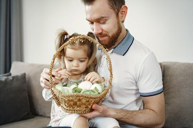 Pai com barba. menina segurando uma cesta. pai e filha sentados no sofá.