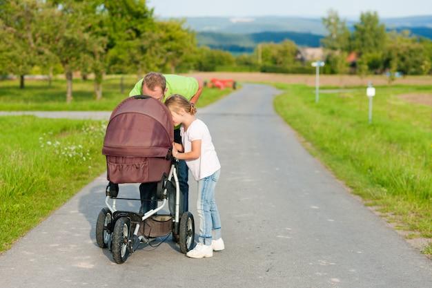 Pai com criança e carrinho de bebê