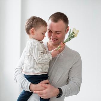 Pai com criança segurando flor