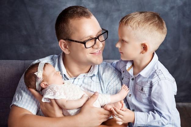 Pai com crianças recém-nascidas e um irmão mais velho. família feliz com filhos em casa. amor, confiança e ternura. família feliz