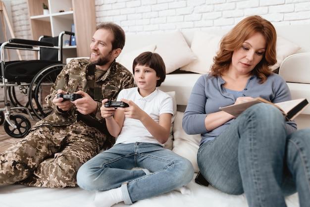 Pai com deficiência está jogando com seu filho no console.