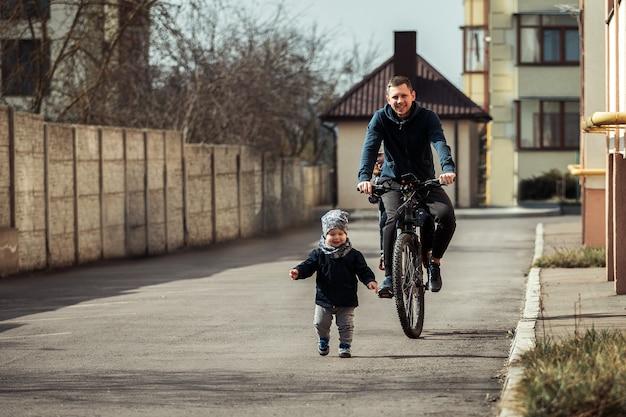 Pai com dois filhos em bicicletas