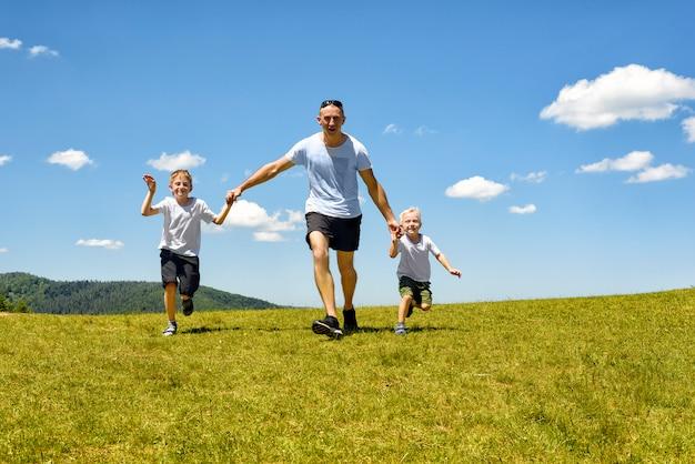 Pai com duas crianças correndo de mãos dadas no campo verde