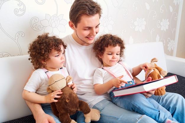 Pai com duas filhas gêmeas lendo um livro no sofá da sala ensinando crianças a ler uma família feliz