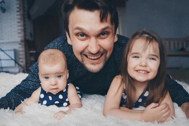 Pai com duas meninas, deitado no chão. homem abraçando uma criança.