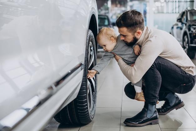 Pai com filha bebê em um showroom de carros