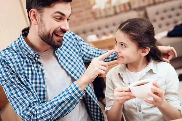 Pai com filha comendo bolos no refeitório.