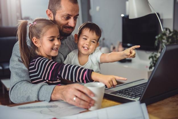 Pai com filha e filho no colo