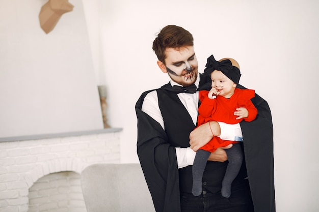 Pai com filha em fantasias e maquiagem. família se prepara para a celebração do halloween.