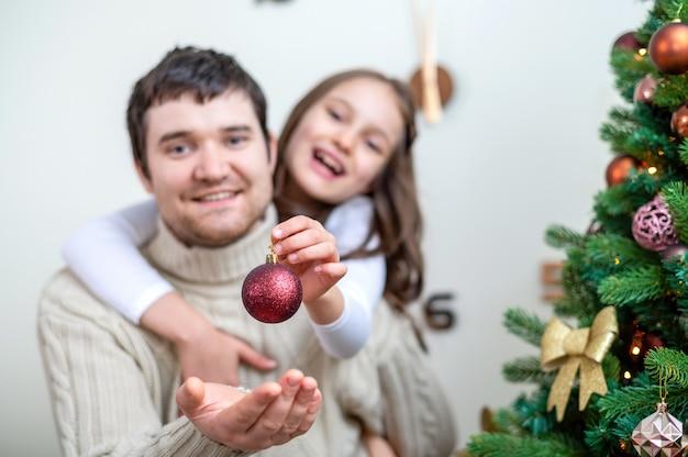 Pai com filha está decorando a árvore de natal em casa. ideia de família feliz