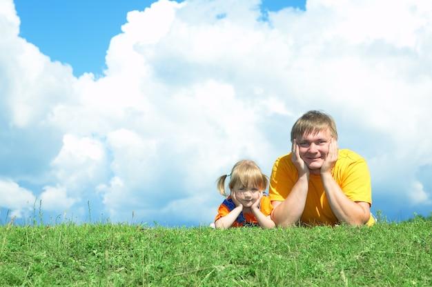 Pai com filha na grama verde sob o céu com nuvens