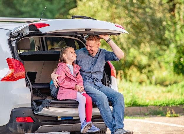Pai com filha sentado no porta-malas do carro depois da escola