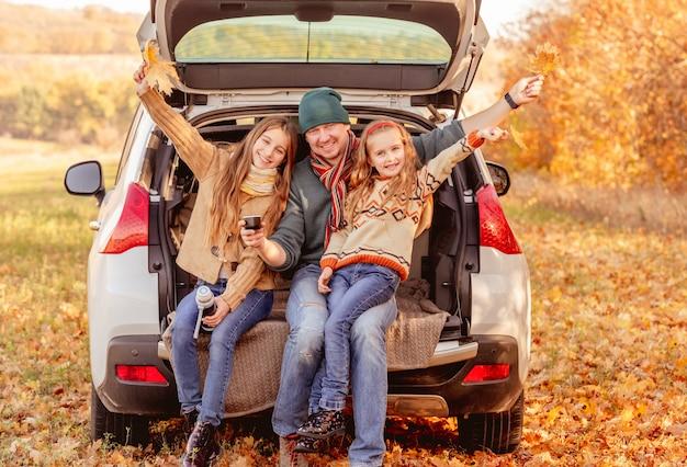 Pai com filhas no outono